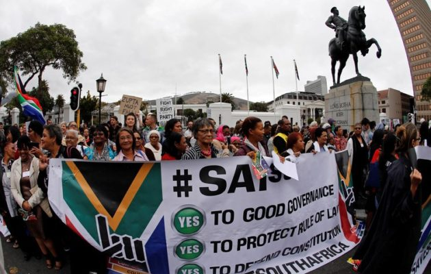 Demonstrators protest against the firing of Finance Minister Pravin Gordhan, outside Parliament in Cape Town. [Reuters/Mike Hutchings